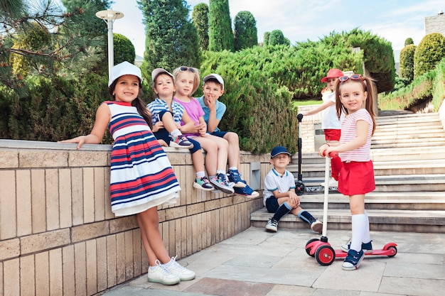 Koncepcja mody dla dzieci. grupa nastolatków chłopców i dziewcząt, pozowanie w parku. kolorowe ubrania dla dzieci, styl życia, koncepcje modnych kolorów.