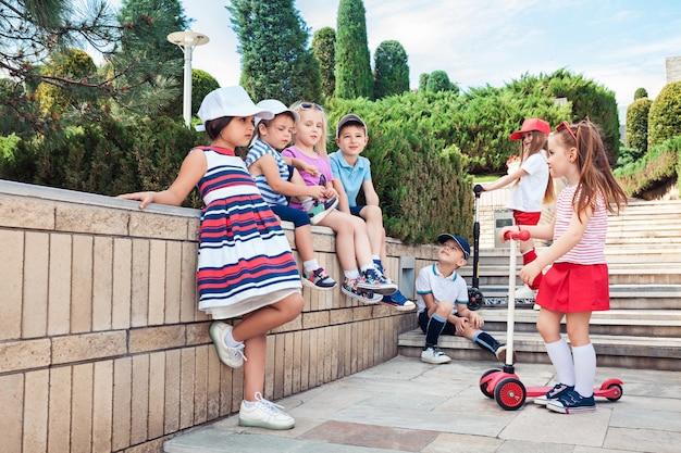 Koncepcja mody dla dzieci. grupa nastolatków chłopców i dziewcząt, pozowanie w parku