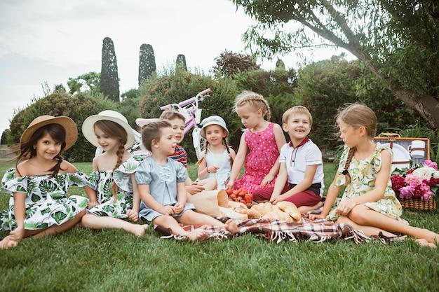 Koncepcja mody dla dzieci. grupa nastolatków chłopców i dziewcząt siedzących na zielonej trawie w parku. kolorowe ubrania dla dzieci, styl życia, koncepcje modnych kolorów.