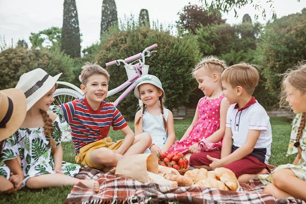 Koncepcja mody dla dzieci. grupa nastolatków chłopców i dziewcząt siedzi na zielonej trawie w parku. kolorowe ubrania dla dzieci, styl życia, koncepcje modnych kolorów.