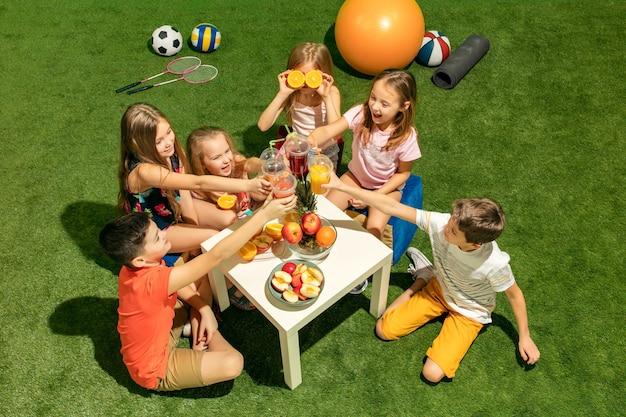Koncepcja mody dla dzieci. grupa nastolatków chłopców i dziewcząt siedzi na zielonej trawie w parku.