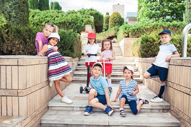 Koncepcja mody dla dzieci. grupa nastoletnich chłopców i dziewcząt pozujących w parku. kolorowe ubrania dla dzieci, styl życia, koncepcje modnych kolorów.