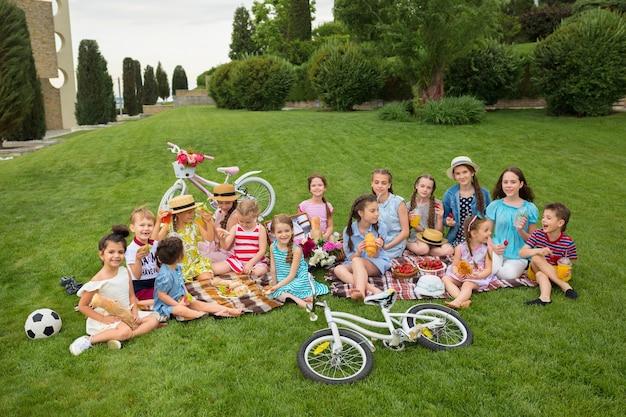 Koncepcja mody dla dzieci. grupa nastoletnich dziewcząt siedzi na zielonej trawie w parku. kolorowe ubrania dla dzieci, styl życia, koncepcje modnych kolorów.