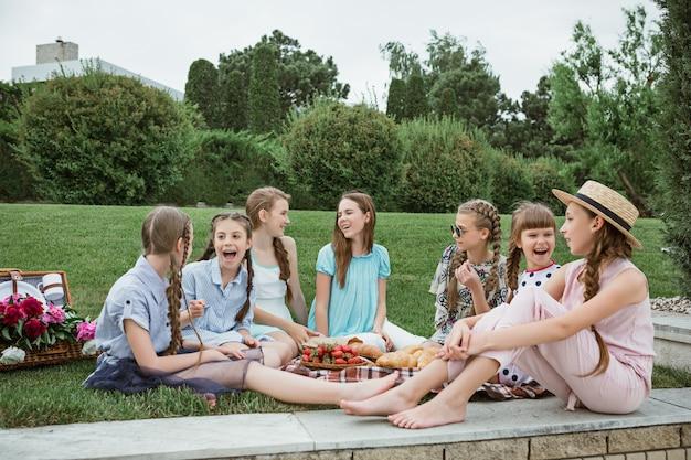Koncepcja mody dla dzieci. grupa nastoletnich dziewcząt siedzi na zielonej trawie w parku