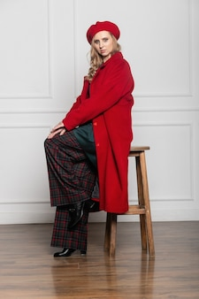 Koncepcja mody i glamour - stylowa kobieta w berecie i płaszczu na jasnym tle. płaszcz, beret, ubrania, styl, moda, uroda, młoda kobieta