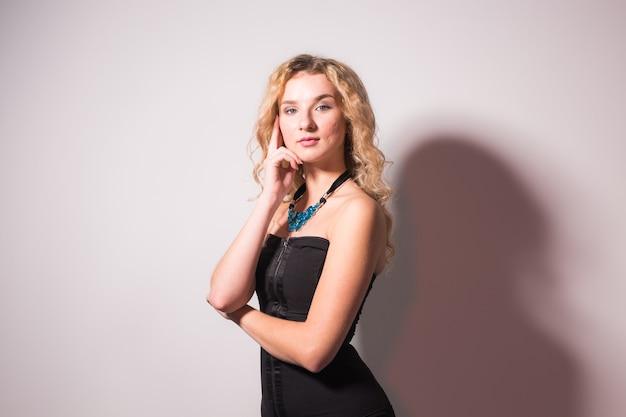 Koncepcja mody i modelu - piękna młoda seksowna blond kobieta w czarnej sukience pozuje na białej ścianie z miejscem na kopię
