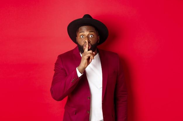 Koncepcja mody i partii. afroamerykanin w eleganckim kapeluszu hushing, prosząc o zachowanie tajemnicy, przygotowując niespodziankę, stojąc na czerwonym tle.