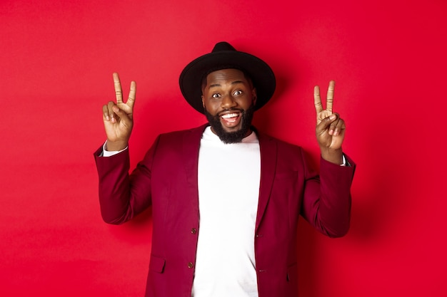 Koncepcja mody i partii. przystojny murzyn bawi się, pokazując znaki pokoju i uśmiechając się, stojąc w kapeluszu na czerwonym tle.