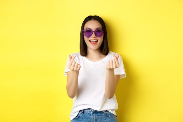 Koncepcja mody i stylu życia. atrakcyjna azjatka w okularach w kształcie serca, pokazująca serduszka i uśmiechnięta szczęśliwa do kamery, stojąca na żółtym tle.