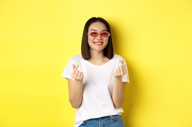 Koncepcja mody i stylu życia. atrakcyjna azjatykcia kobieta w stylowych okularach przeciwsłonecznych, pokazując serduszka i uśmiechając się zadowolony do kamery, stojąc na żółtym tle.