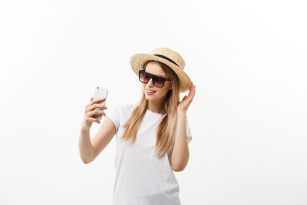 Koncepcja mody i stylu życia: ładna młoda kobieta w kapeluszu, okulary przeciwsłoneczne, robienie sobie zdjęcia przez telefon komórkowy na białym tle nad białym tłem.