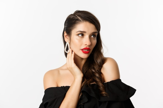 Koncepcja mody i urody. zbliżenie: elegancka kobieta w czarnej sukience, pokazująca kolczyki i wyglądająca zmysłowo, czerwona szminka i makijaż na białym tle