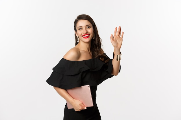 Koncepcja mody i zakupów. stylowa młoda kobieta z makijażem glamour, ubrana w czarną sukienkę, trzymając cyfrowy tablet i witając się, machając ręką, aby cię przywitać, białe tło.