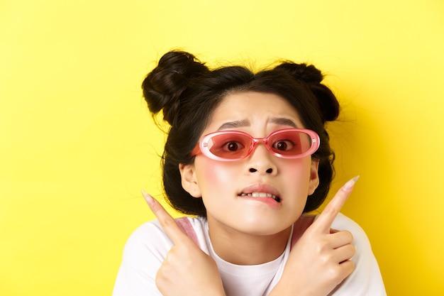 Koncepcja mody letniej. ujęcie w głowę zmartwionej niezdecydowanej azjatki, wskazującej palcami w bok i pokazującej dwa sposoby, nie mogę wybrać, w okularach przeciwsłonecznych.