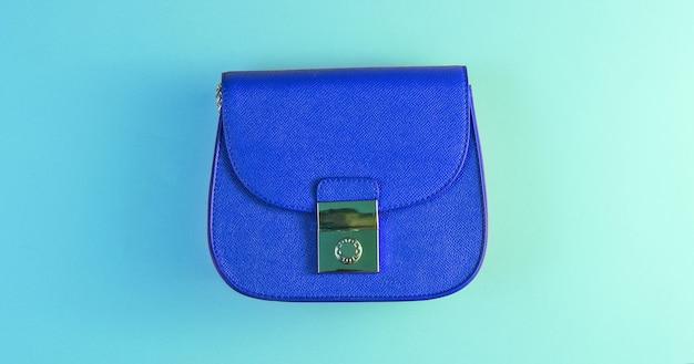 Koncepcja mody minimalizmu. niebieska mini torebka z holograficznym światłem w kolorze zielonego gradientu. widok z góry