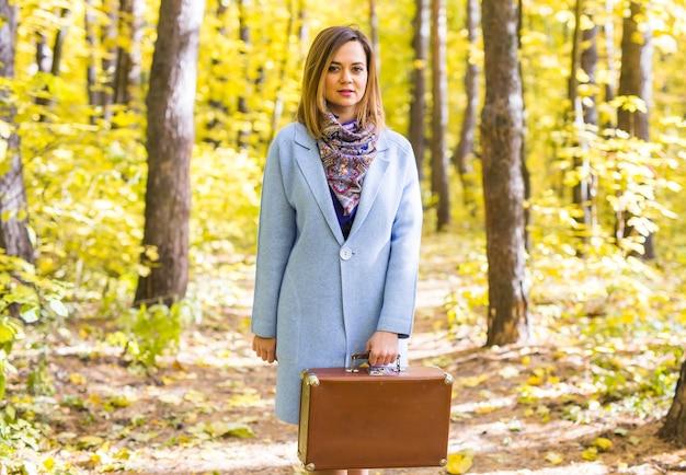 Koncepcja mody, sezonu i ludzi - szczęśliwa młoda kobieta jedzie w podróż z walizką retro na