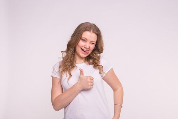 Koncepcja mody, stylu i gestów. mrugając ładna kobieta na białym pokazując kciuk do góry na białym tle.