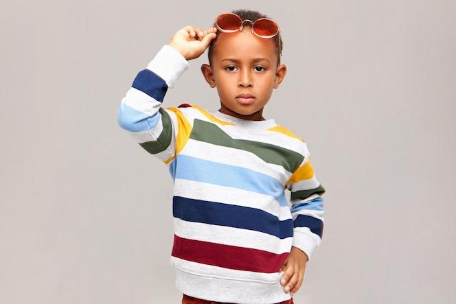 Koncepcja mody, stylu, odzieży dziecięcej i akcesoriów dla dzieci. poważny, pewny siebie afroamerykanin modelujący przed pustą ścianą ubrany w sweter w paski i różowe okulary na głowie