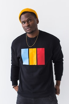 Koncepcja mody ulicznej młodzieży - portret pewny siebie seksowny murzyn w stylowej bluzie na białym tle