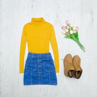 Koncepcja mody. żółty golf, niebieska spódnica, buty i różowe tulipany. drewniane tła