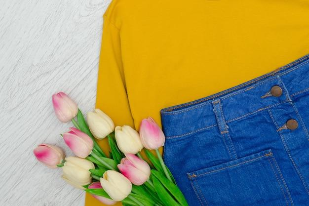 Koncepcja mody. żółty sweter, niebieska spódnica i różowe tulipany.