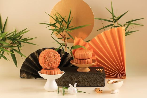 Koncepcja mooncake na jasnym tle z bambusa. żółty tort księżycowy koncepcja na festiwalu w połowie jesieni. mooncake popularny jako kue bulan.