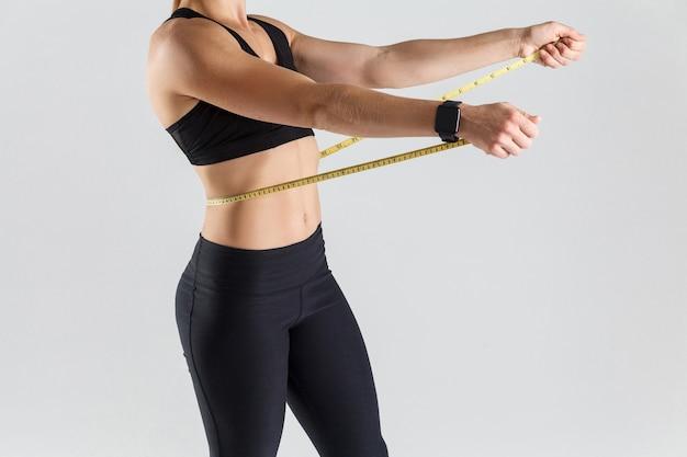 Koncepcja motywacji kobieta trzymająca centymetr na brzuchu
