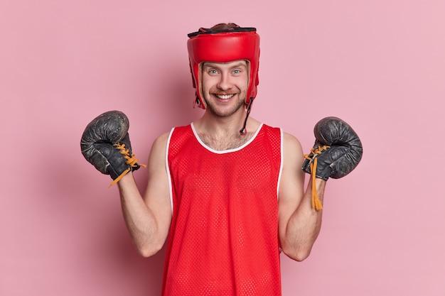 Koncepcja motywacji sportu ludzi. pozytywny mężczyzna ma trening na siłowni, nosi ochronne nakrycie głowy, rękawice bokserskie, koszulka ma wesoły wyraz po wygranej grze sportowej
