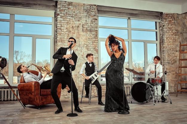 Koncepcja muzyczna. próba występu zespołu muzycznego. emocjonalni muzycy zapalają się na próbie.