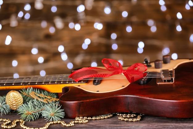 Koncepcja muzyki boże narodzenie. gitara z dekoracją na drewnianym stole