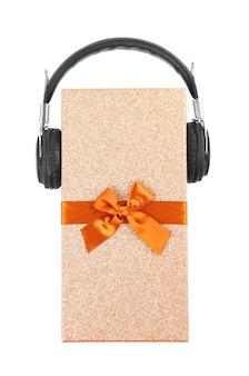 Koncepcja muzyki boże narodzenie. prezent ze słuchawkami na białym tle