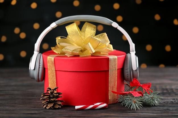 Koncepcja muzyki boże narodzenie. prezent ze słuchawkami na drewnianym stole