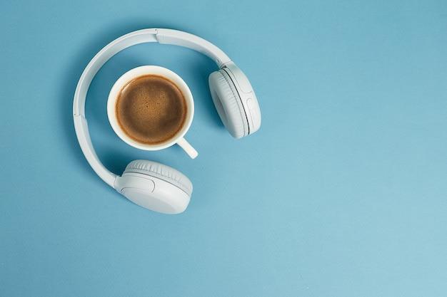 Koncepcja muzyki lub podcastu ze słuchawkami i filiżanką kawy. widok z góry, płaski układ