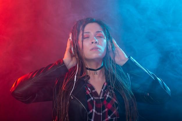 Koncepcja muzyki, melomana i ludzi - szczęśliwa kobieta z dredami słuchając muzyki i ciesząc się nią