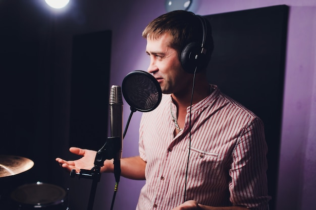 Koncepcja muzyki, show biznesu, ludzi i głosu - wokalista ze słuchawkami i mikrofonem śpiewa piosenkę w studiu nagrań dźwiękowych.