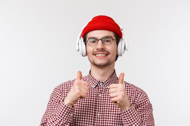 Koncepcja muzyki, technologii i ludzi. close-up portret zadowolony zadowolony młody kaukaski brodaty mężczyzna hipster w okularach i czapka, pokaż kciuki w górze jak słuchanie muzyki w słuchawkach