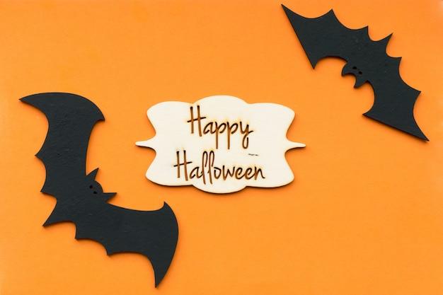 Koncepcja na halloween, nietoperze na pomarańczowo z frazą happy halloween