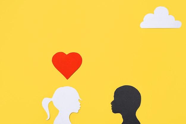 Koncepcja na walentynki, miłość międzyrasowa. sylwetki dziewczyny i chłopca, żółte tło. karta miłości twórczej sztuki. leżał na płasko, widok z góry, miejsce na kopię