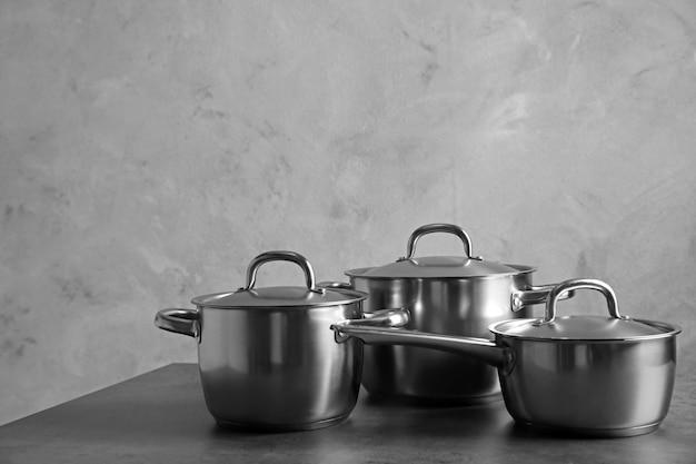 Koncepcja naczynia kuchenne. rondle ze stali nierdzewnej na stole i szarej teksturowanej ścianie