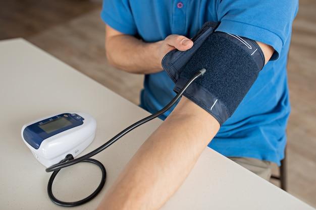 Koncepcja nadciśnienia. mężczyzna mierzy ciśnienie krwi z monitorem w domu. zbliżenie dłoni