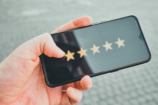 Koncepcja najwyższej oceny w postaci pięciu gwiazdek na wyświetlaczu smartfona w rękach.