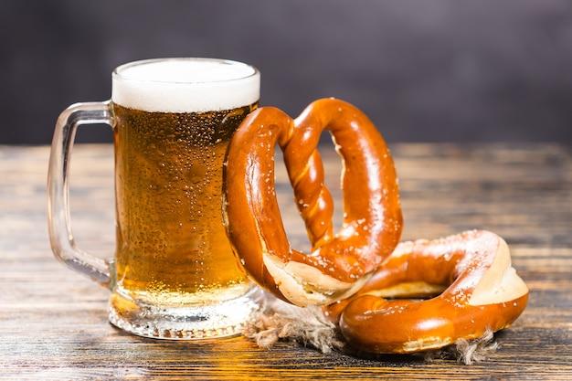 Koncepcja napojów i żywności - szklanka piwa i bułeczki na stole z drewna