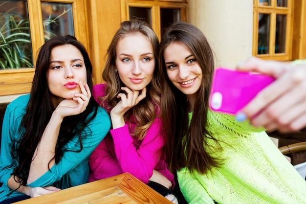 Koncepcja napojów, przyjaźni, technologii i ludzi - trzy szczęśliwe ładne kobiety z filiżankami, siedząc przy stole i biorąc selfie ze smartfonem w kawiarni. jasne, słoneczne kolory.