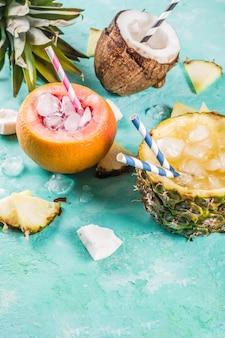 Koncepcja napoju wakacyjnego, zestaw różnych tropikalnych koktajli lub soków w ananasie, grejpfrucie i kokosie z lodem, jasnoniebieski beton