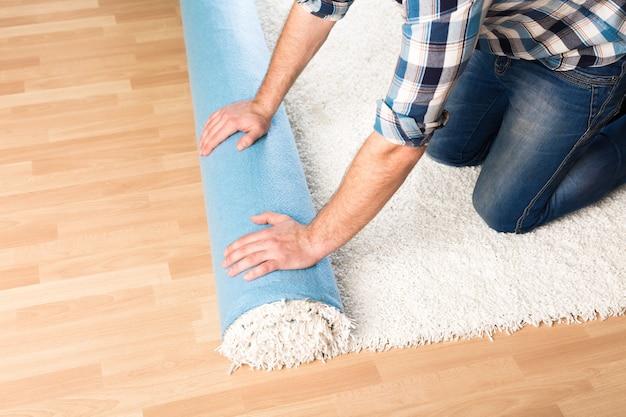 Koncepcja naprawy, budowy i domu - zbliżenie męskich rąk toczących dywan