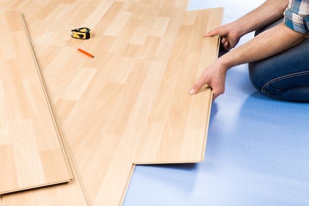 Koncepcja naprawy, budowy i domu - zbliżenie męskich rąk z drewnianymi podłogami
