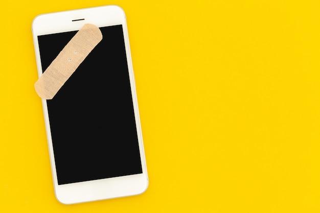 Koncepcja naprawy smartfona. telefon z pustym ekranem na żółtym tle widok z góry