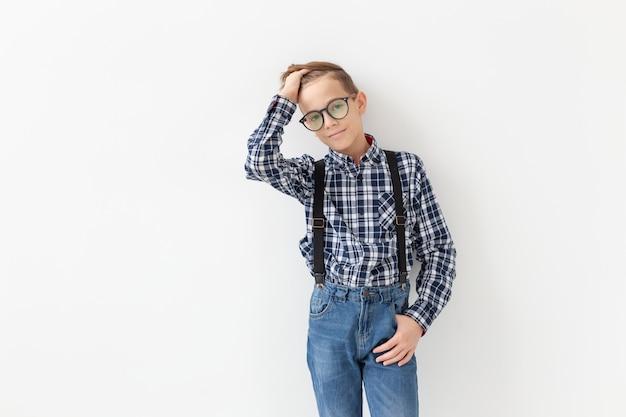 Koncepcja nastolatek, dzieci i moda - dzieciak ubrany w koszulę w kratę pozowanie na białym tle