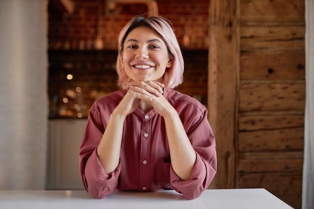 Koncepcja nastolatka, młodość, styl i wyrażanie siebie. portret pozytywna szczęśliwa nastolatka z różowawą fryzurą boba i piercingiem twarzy relaksujący w pomieszczeniu