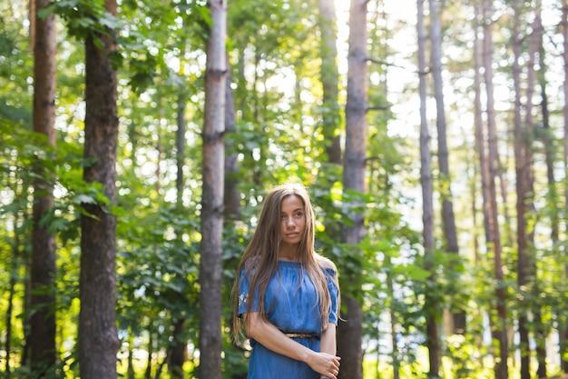Koncepcja natura, lato i ludzie - portret romantycznej młodej kobiety w lesie.